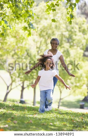 Grandmother and granddaughter running in park and smiling - stock photo