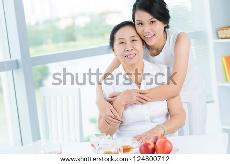 Grandmother and granddaughter sitting in the room and embracing