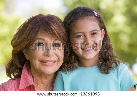 Grandmother and granddaughter smiling - stock photo