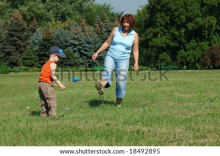 Grandmother and grandson are playing football on the green grass