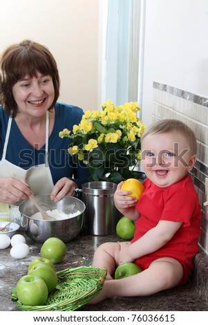 Grandmother and grandson in the kitchen baking cake - stock photo