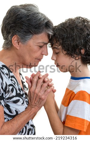 Grandmother and grandson praying together in their daily Christian devotional. Hispanic family practising their faith in Jesus and in God praying together. - stock photo