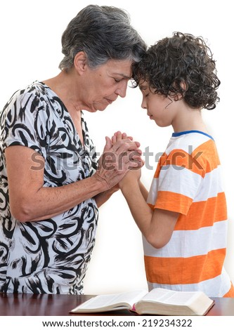 Grandmother and grandson praying together in their daily Christian devotional. Hispanic family practising their faith in Jesus and in God praying together.