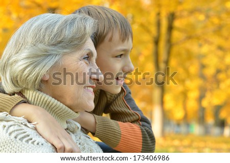 Grandmother and grandson take a walk during the fall of the leaves in the park - stock photo