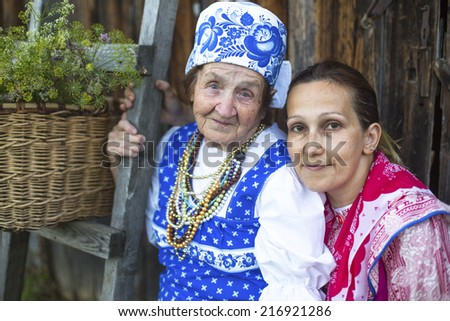 Grandmother and her daughter in ethnic clothes outdoor in the countryside. - stock photo