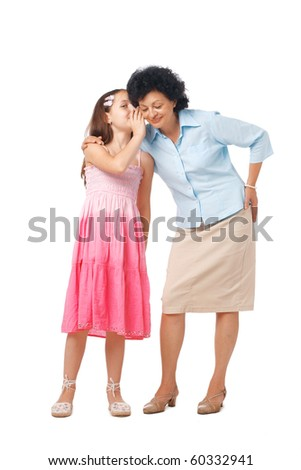 Grandmother and her grand daughter whispering something into her ear, full length. - stock photo