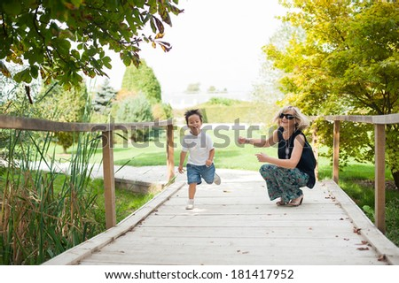 Grandmother and her grandson are having fun in the park - stock photo