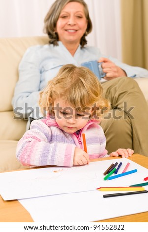 Grandmother and little girl drawing together with pencils at home