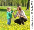 Grandmother and little granddaughter playing on the meadow of yellow dandelions - stock photo