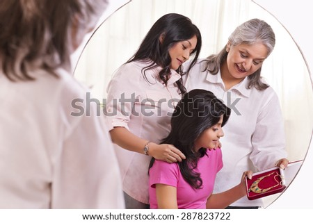 Grandmother and mother gifting jewelry to the girl - stock photo
