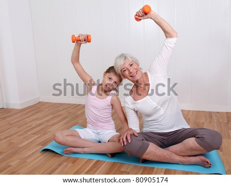 Grandmother and young girl doing fitness exercises - stock photo