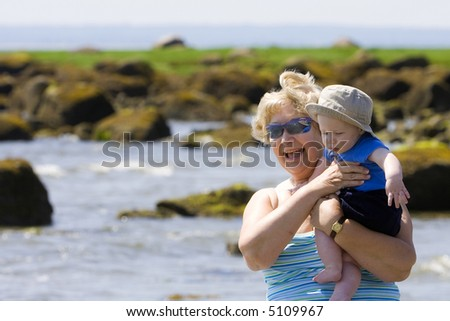 Grandmother at the beach on a sunny day - stock photo