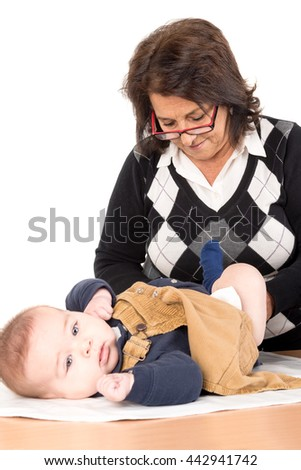 Grandmother changing baby diaper isolated in white