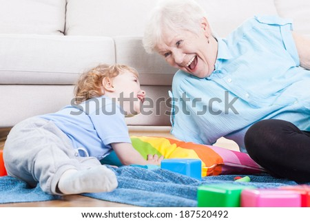 Grandmother cheerfully playing with her grandson indoors - stock photo