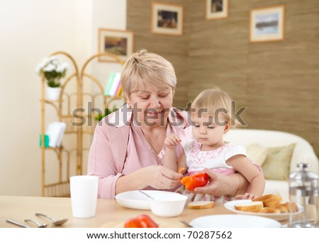 grandmother feeding her little baby granddaughter at home