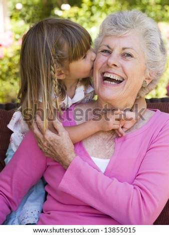 Grandmother getting a kiss from granddaughter - stock photo