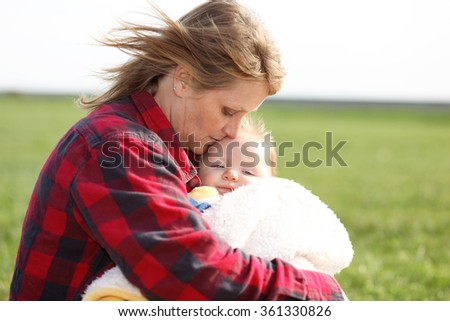 Grandmother giving her grandson some loving care. - stock photo
