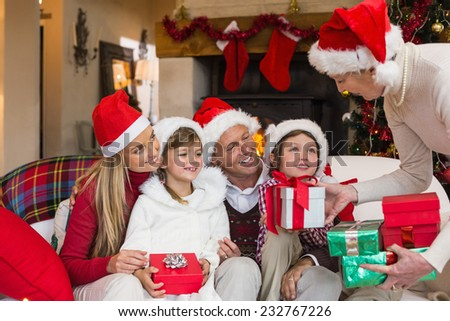 Grandmother giving several gifts to her family at home in the living room - stock photo