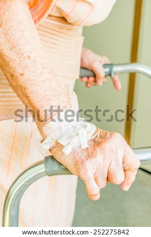 Grandmother hands using a walker as support - stock photo
