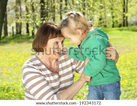 Grandmother has fun with a pretty little granddaughter on the background of yellow dandelions. - stock photo