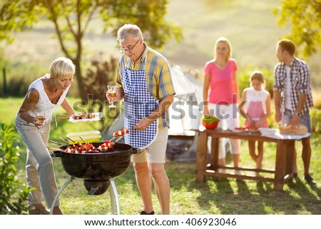 grandmother help grandfather baked on campfire for family