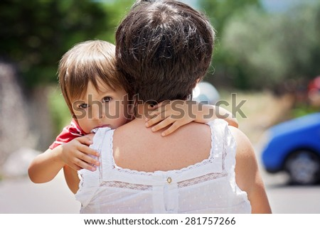Grandmother, holding and hugging her grandson, little cute caucasian boy, outdoors, tender portrait