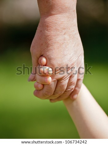 Grandmother holding granddaughter's hand closeup - stock photo