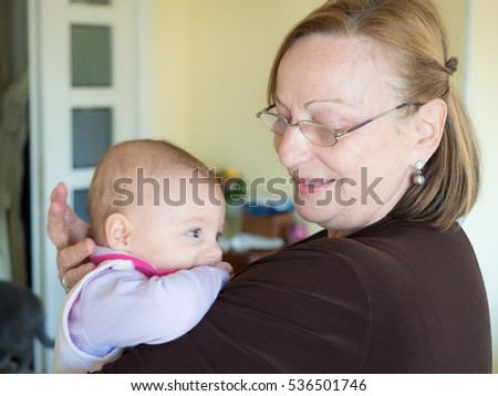 Grandmother holding her granddaughter in her hands, having some fun.