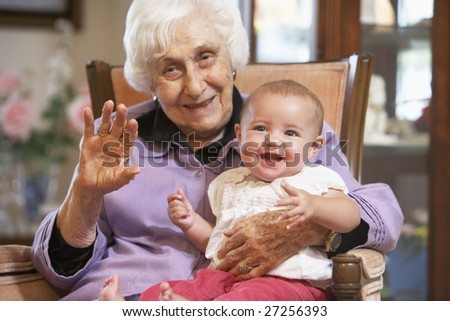 Grandmother holding her granddaughter on lap - stock photo