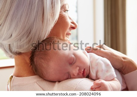 Grandmother Holding Sleeping Newborn Baby Granddaughter - stock photo