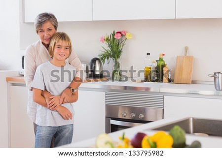 Grandmother hugging her grandson in her arms in kitchen - stock photo