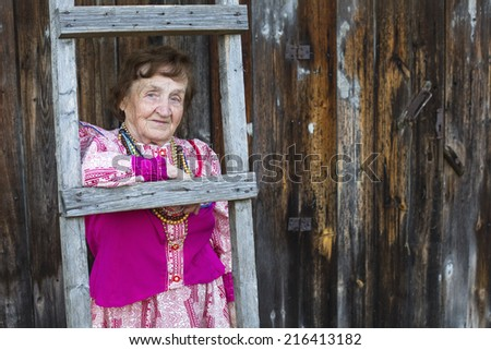 Grandmother in ethnic clothes in the yard of his rural home. - stock photo