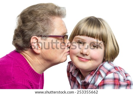 Grandmother kisses granddaughter on cheek isolated on white background - stock photo