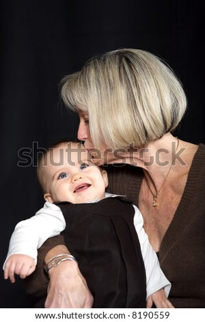 Grandmother Kissing Granddaughter on Forehead - stock photo