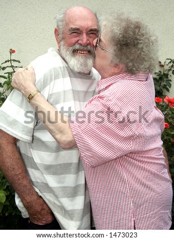Grandmother kissing her husband - stock photo