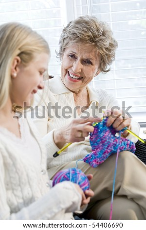 Grandmother knitting with granddaughter, focus on senior woman - stock photo