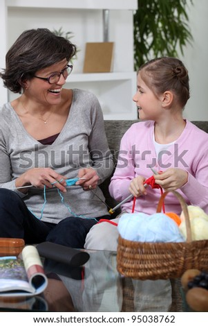 Grandmother knitting with her granddaughter - stock photo