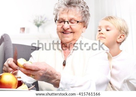 Grandmother looks after the child. Grandmother to grandchild picks an apple peel - stock photo