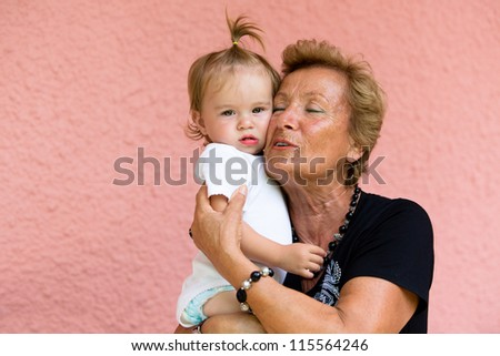 Grandmother loves her grandkid while showing her true feelings. - stock photo