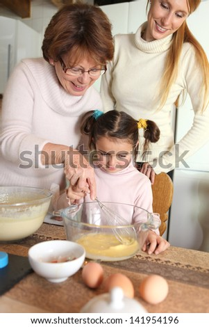 grandmother making crepes with little granddaughter - stock photo