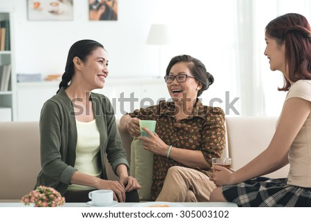Grandmother, mother and daughter drinking tea and having good time together - stock photo