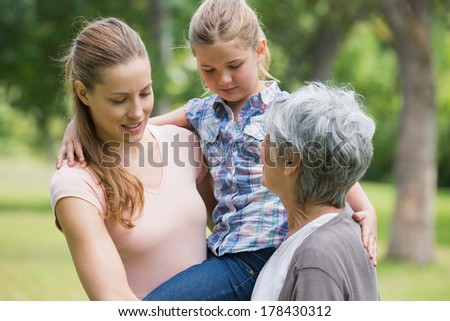 Grandmother mother and daughter standing at the park - stock photo