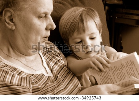 grandmother read the book for her grandson. sepia - stock photo