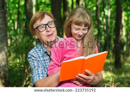 Grandmother reading a book girl - stock photo