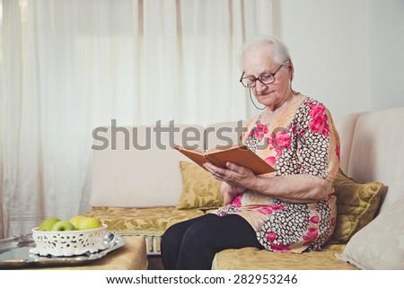Grandmother reading alone - stock photo