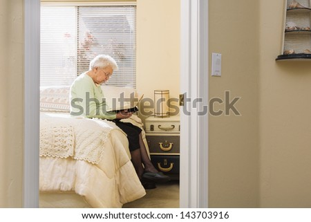 Grandmother Reading Bible in Bedroom (Distant View Through a Door) - stock photo