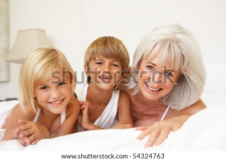 Grandmother Relaxing On Bed With Grandchildren - stock photo