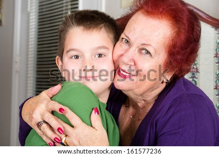 Grandmother's Love to her eight years old grandson, she hugs him tightly with a cheek to cheek touch while looking at you - stock photo