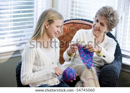 Grandmother teaching granddaughter how to knit - stock photo
