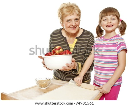 grandmother teaching her granddaughter bake apple pie, white background - stock photo